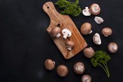 Funghi prataioli dei funghi su un fondo nero e su un bordo di legno Ingredienti per pranzo Spazio libero per testo Vista superior fotografia stock