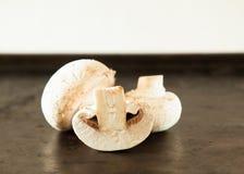 3 funghi prataioli si espandono rapidamente sulla forno-pentola nera con il pomodoro e l'insalata Immagini Stock Libere da Diritti