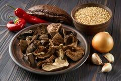 Funghi secchi e riso sbramato in piatti rustici dell'argilla immagini stock