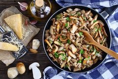 Funghi trifolati or fried porcini sprinkled with parsley in skillet with kitchen towel on old dark wooden table Royalty Free Stock Image