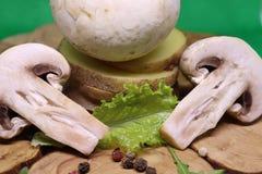 Fungo prataiolo crudo con le patate su uno schiarimento di legno fotografia stock libera da diritti