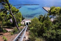 Funicular που φέρνει τους φιλοξενουμένους επάνω οι απότομοι απότομοι βράχοι σε Kanoni στο ελληνικό νησί της Κέρκυρας Στοκ εικόνες με δικαίωμα ελεύθερης χρήσης