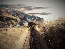 A Funicular in a Seaside Town. A moving funicular on the back drop of a seaside town during the summer next to the sand and the sea stock photography