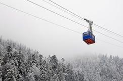 Funikuläre Überfahrt über dem schneebedeckten Wald Stockfotografie