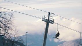 Funikuläres timelapse hebt Skifahrer und Snowboarder unter den Bergen und den Wolken an stock video