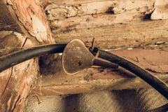 Funil oxidado velho para a água que pendura em um prego na garagem Mangueira preta para drenar a gasolina imagens de stock royalty free