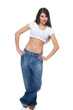 Funk girl in big jeans. Beautiful funk girl in oversize jeans standing with hands on hips, over white background stock photos
