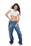 Funk girl in big jeans. Beautiful funk girl in oversize jeans standing over white background with flying hair stock photography