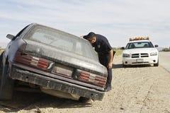 Funkcjonariusz Policji Patrzeje W Zaniechanego samochód Zdjęcie Stock