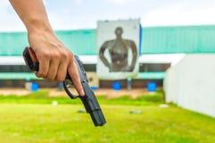Funkcjonariusz policji trzyma egzekwowanie prawa pistoletowy w akademia krótkopędzie obrazy royalty free