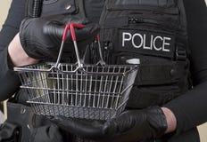 Funkcjonariusz policji trzyma małego drucianego kosz fotografia stock
