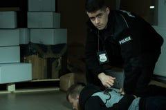 Funkcjonariusz policji uderzająca przestępca obraz stock