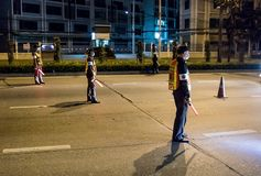 Funkcjonariuszi policji sprawdzają samochody na Bangkok nocy drodze obrazy stock
