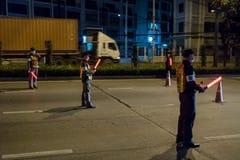 Funkcjonariuszi policji sprawdzają samochody na Bangkok nocy drodze zdjęcia stock
