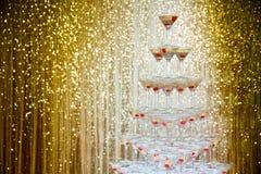 Funkelnde Champagnerpyramide, Turm von Gläsern an der Partei vor goldener Wand Lizenzfreies Stockfoto