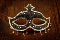 Funkelnde Karnevalsmaske auf Holztisch Stockfotografie