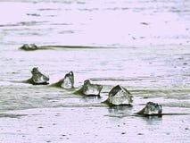 funkelnde Scherben des gebrochenen Eises stehen heraus auf dem gefrorenen See hervor Der Lichteffekt tritt auf Stockfoto