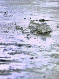 funkelnde Scherben des gebrochenen Eises stehen heraus auf dem gefrorenen See hervor Der Lichteffekt tritt auf Stockfotos