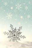 Funkelnde Schneeflocke im Schnee Stockfotografie