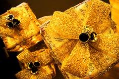 3 funkelnde Weihnachtspakete, mit großen Goldbögen und Glocken Stockfotografie