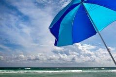 Funkelnder Ozean mit Strand-Regenschirm Lizenzfreies Stockfoto