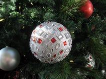 Funkelnder perlenbesetzter silberner Ball, der am Weihnachtsbaum hängt stockfotos
