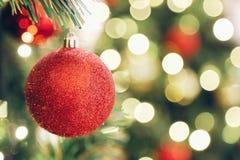 Funkelnder roter Ball des Funkelns des Fokus auf Unschärfe Weihnachtsbaum und Licht bokeh im Hintergrund Stockbilder