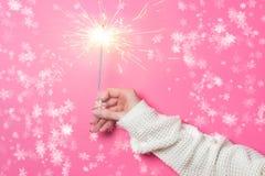 Funkelndes Bengal-Feuer in einer Frau ` s Hand auf einem rosa Hintergrund Weihnachtsniederlassung und -glocken Lizenzfreie Stockfotografie