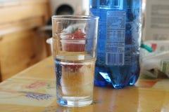 Funkelndes Wasser in einem Glas mit Flasche im Hintergrund Lizenzfreie Stockfotos