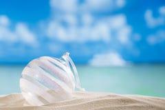 Funkelnweihnachtsglaskugel auf Strand mit Meerblickhintergrund Lizenzfreies Stockfoto