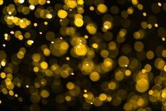 Funkelnweinlese beleuchtet Hintergrund dunkles Gold und Schwarzes defocuse Lizenzfreie Stockfotografie