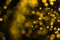 Funkelnweinlese beleuchtet Hintergrund dunkles Gold und Schwarzes defocuse Stockbild