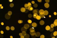 Funkelnweinlese beleuchtet Hintergrund dunkles Gold und Schwarzes defocuse Stockfoto
