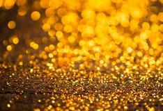 Funkelnweinlese beleuchtet Hintergrund dunkles Gold und Schwarzes defocuse Stockfotos