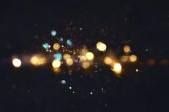 Funkelnweinlese beleuchtet Hintergrund Gold, Blau und Schwarzes defocused Stockfotos