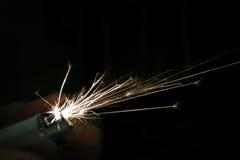 Funken, die vom Feuerzeug über schwarzem Hintergrund kommen Stockfoto