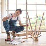 Funktion des jungen Mannes als Heimwerker, zusammenbauende hölzerne Tabelle mit equipm lizenzfreie stockfotos