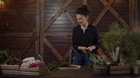 Funktionsduglig blomsterhandlare Woman med julkransen Ung gullig le kvinnaformgivare som förbereder den vintergröna trädkransen f lager videofilmer