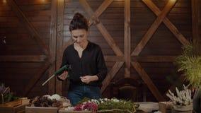 Funktionsduglig blomsterhandlare Woman med julkransen Ung gullig le kvinnaformgivare som förbereder den vintergröna trädkransen f arkivfilmer