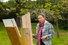 Funktionsduglig det fria för ensam yrkesmässig trendig kvinnlig konstnär i trädgården royaltyfria bilder