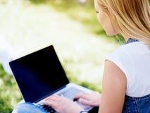 Funktionsduglig det fria för kvinna i en äng med bärbara datorn Arkivfoto