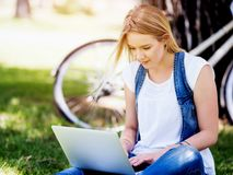 Funktionsduglig det fria för kvinna i en äng med bärbara datorn Royaltyfria Bilder