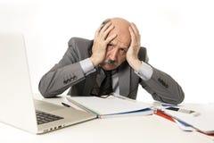 Funktionsduglig stressat för skallig 60-tal för affärsman och frustrerat på skrivbordet för bärbar dator för kontorsdator som ser arkivbild