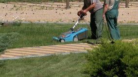 Funktionsdugliga trädgårdsmästare mejar gräset med en elektrisk gräsklippare lager videofilmer