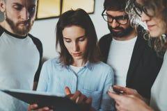 Funktionsdugligt ögonblicksfoto Grupp av unga coworkers som tillsammans använder det elektroniska handlagblocket på den moderna k royaltyfri foto