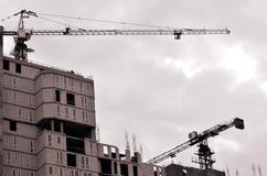 Funktionsdugligt högväxt kraninsidaställe för med högväxta byggnader under konstruktion mot en klar blå himmel Kran- och byggnads Royaltyfri Fotografi