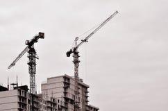 Funktionsdugligt högväxt kraninsidaställe för med högväxta byggnader under konstruktion mot en klar blå himmel Kran- och byggnads Arkivfoto
