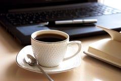 Funktionsdugligt skrivbord med bärbara datorn, anteckningsboken och kaffe Royaltyfri Foto