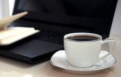 Funktionsdugligt skrivbord med bärbara datorn, anteckningsboken och kaffe Arkivfoton