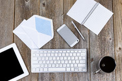 Funktionsdugligt skrivbord med traditionella brevskickandeobjekt och modern tech royaltyfria bilder